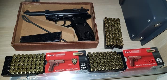A picture of Authorities seized what appears to be a P1/P38 and two boxes of 9mm ammunition.