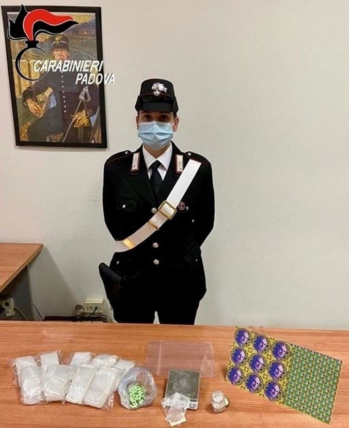 A picture of a masked law enforcement officer stands next to seized narcotics